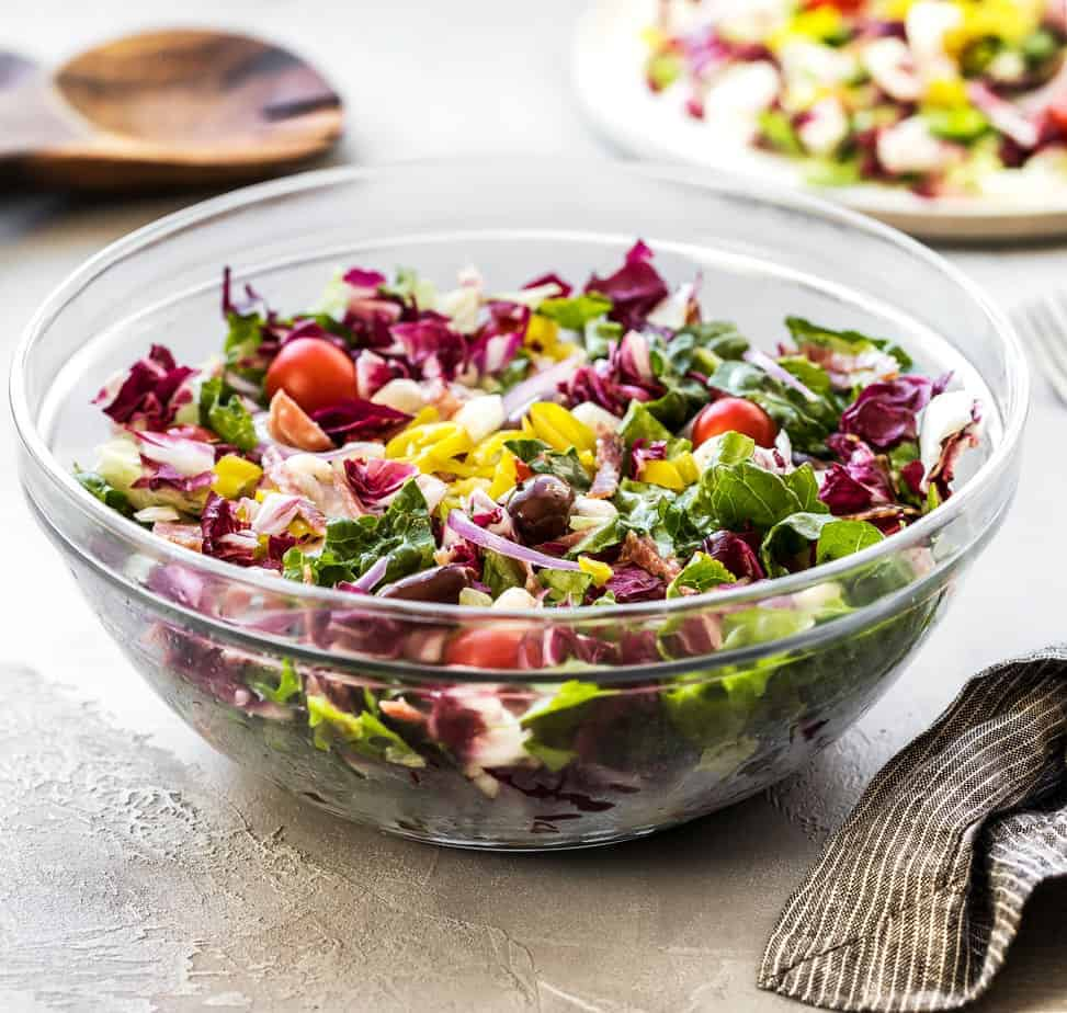 Looking for summer salad recipes? Try this Italian Chopped Salad with Salami & Pepperoncini Peppers! Made of chopped vegetables, herbs, and spices, fresh iceberg lettuce, radicchio, romaine heart, pepperoncini, mozzarella balls, black olives, sugar plum tomatoes, red onion, hard salami, Italian salami, and a homemade Italian Vinaigrette.