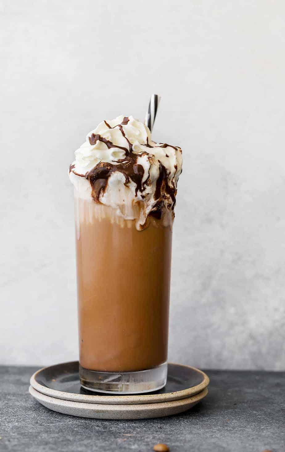 Learn how to make an iced coffee mocha recipe at home. Brewed coffee served with homemade chocolate syrup, ice, and whipped cream.
