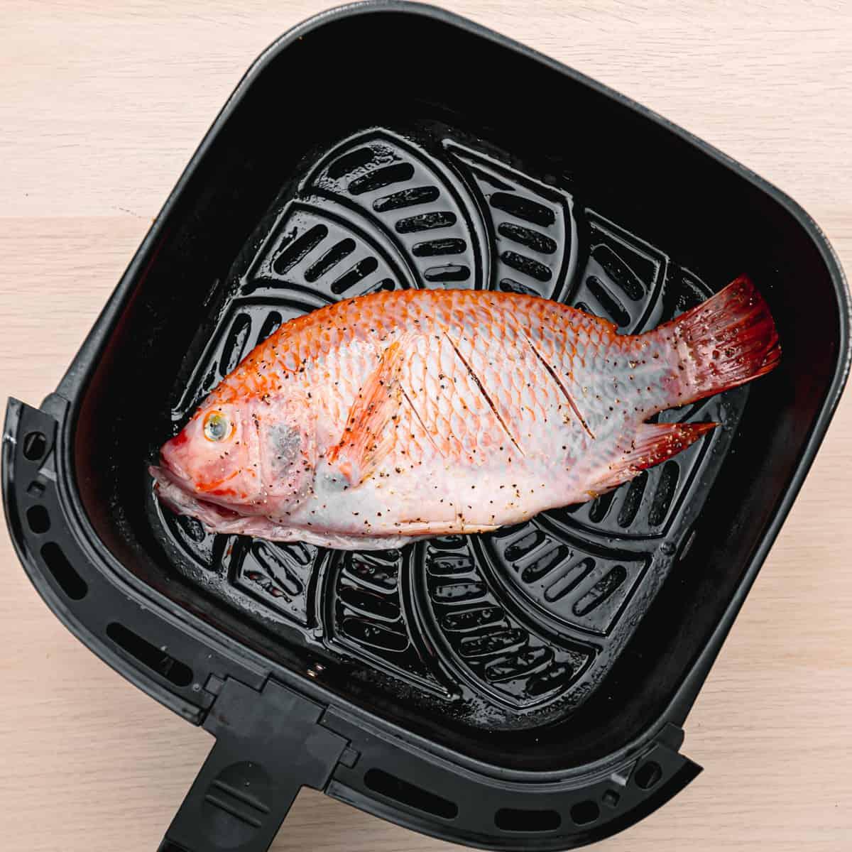 a fish inside an air fryer.