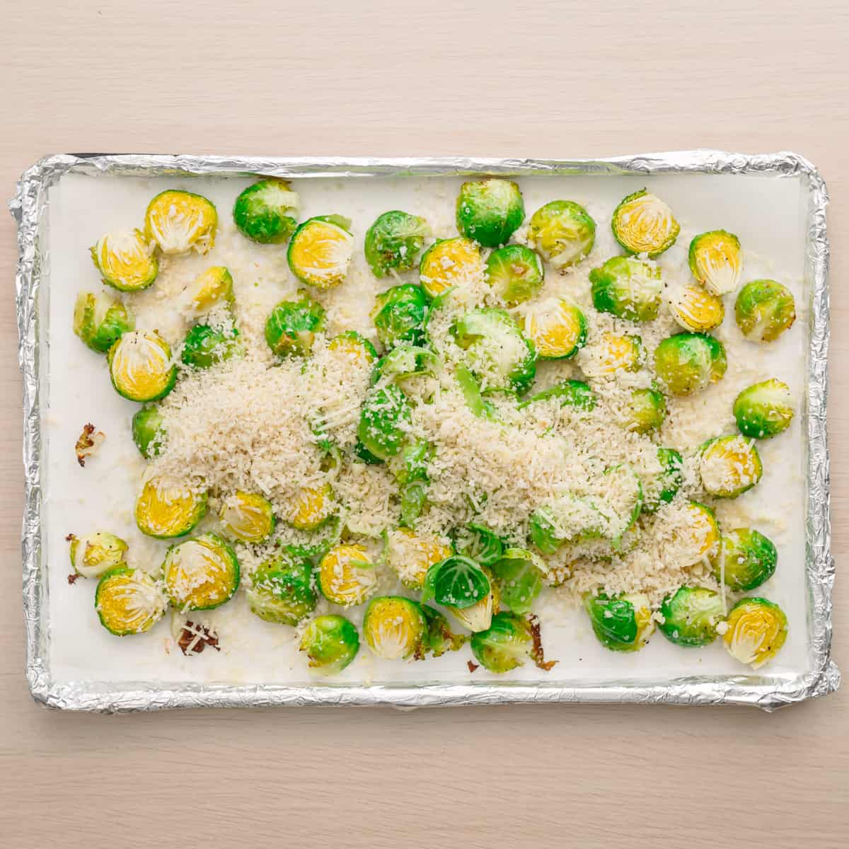 Brussels sprouts with parmesan, panko breadcrumbs on a baking sheet.