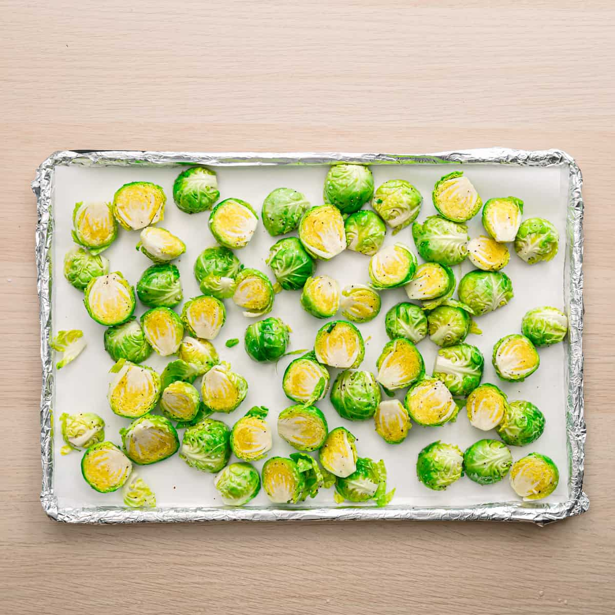 Brussels sprouts on a prepared baking sheet.