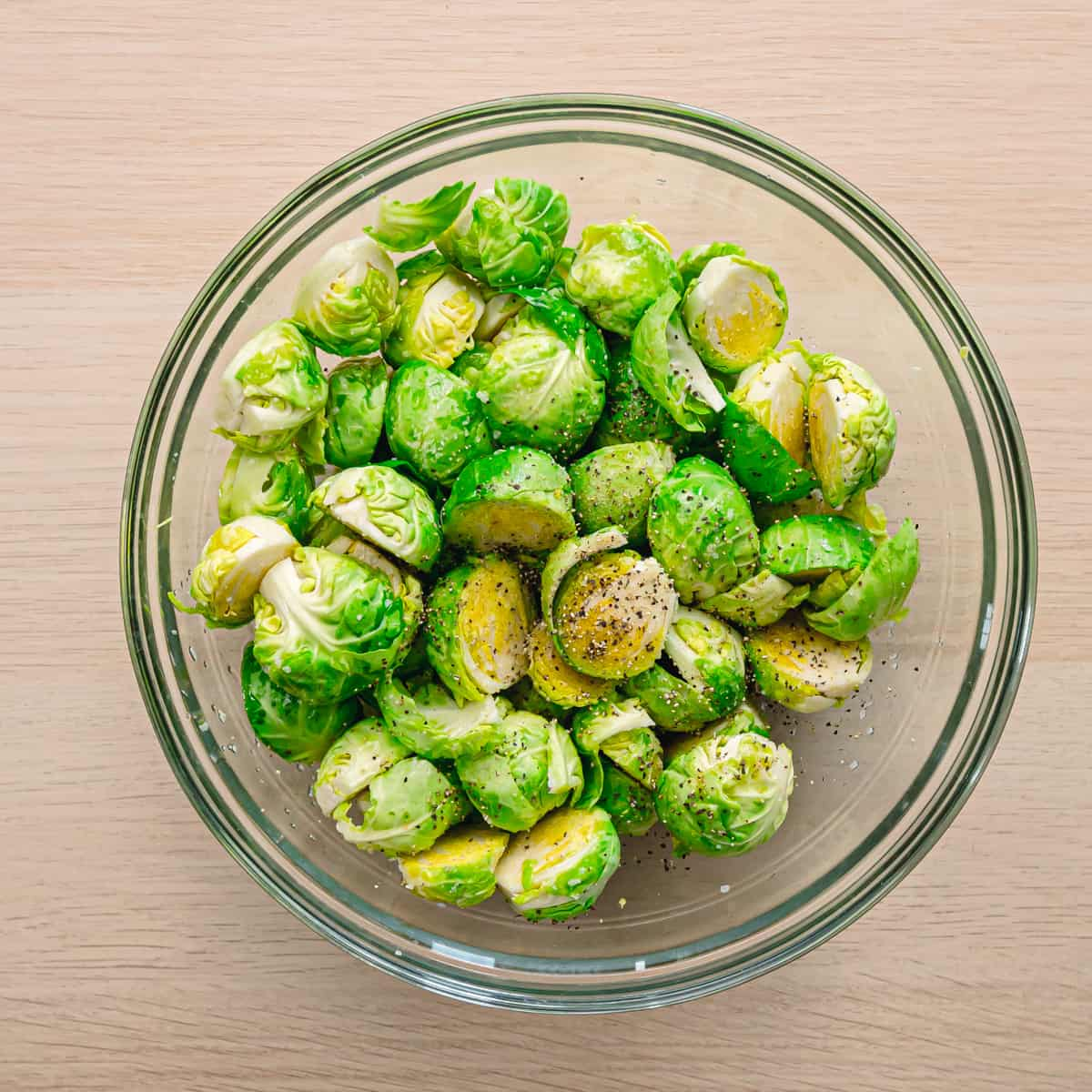 A bowl full of brussels sprouts with kosher salt and black pepper