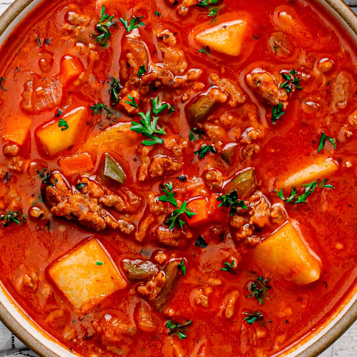 A soup with potato, Italian sausage, vegetables, and tomato broth.