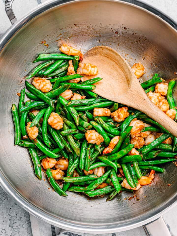 green beans and shrimp in a wok.