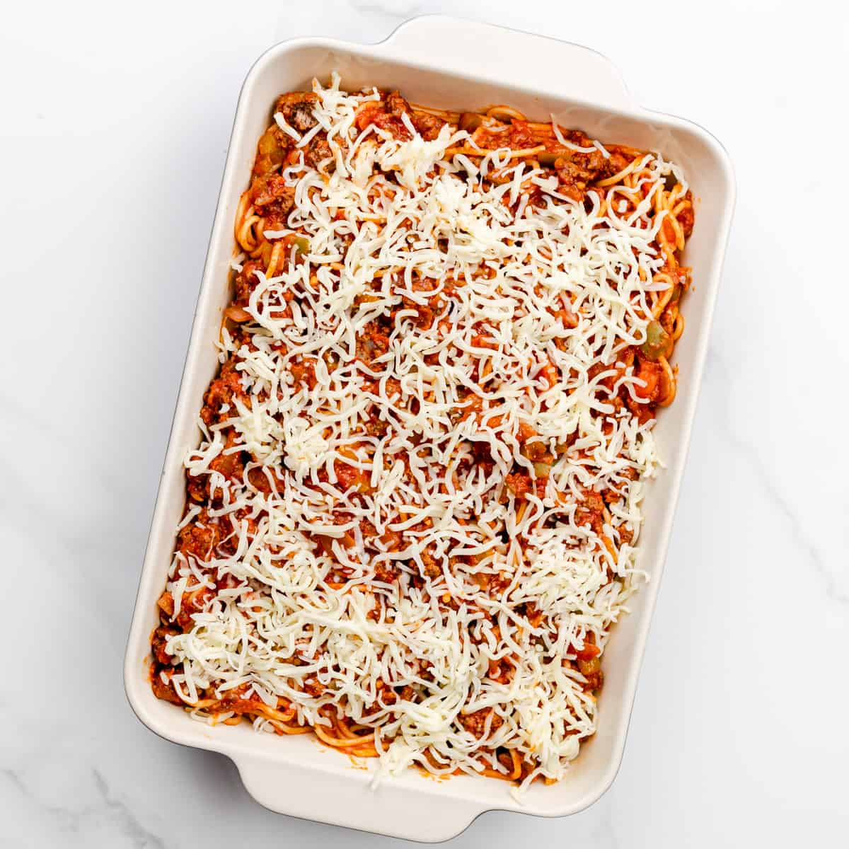 Place half of the spaghetti mixture in a greased 13x9-inch baking dish. Top with half of the shredded mozzarella cheese. Repeat the same process for the other half.
