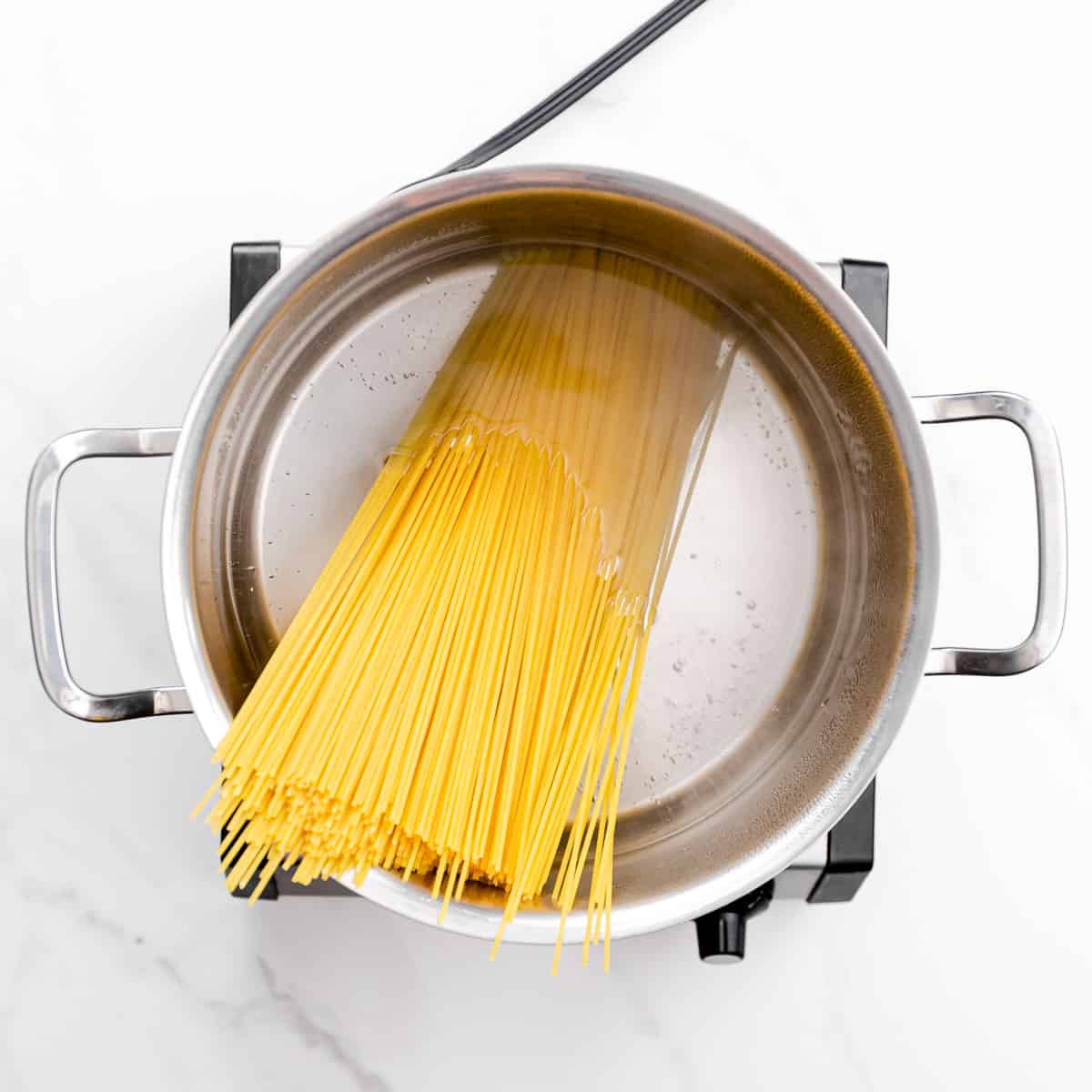 cook the pasta in salted boiling water until it's slightly undercooked.