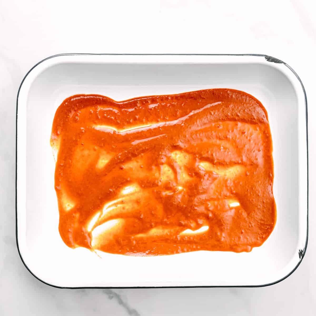 spreading enchilada sauce.
