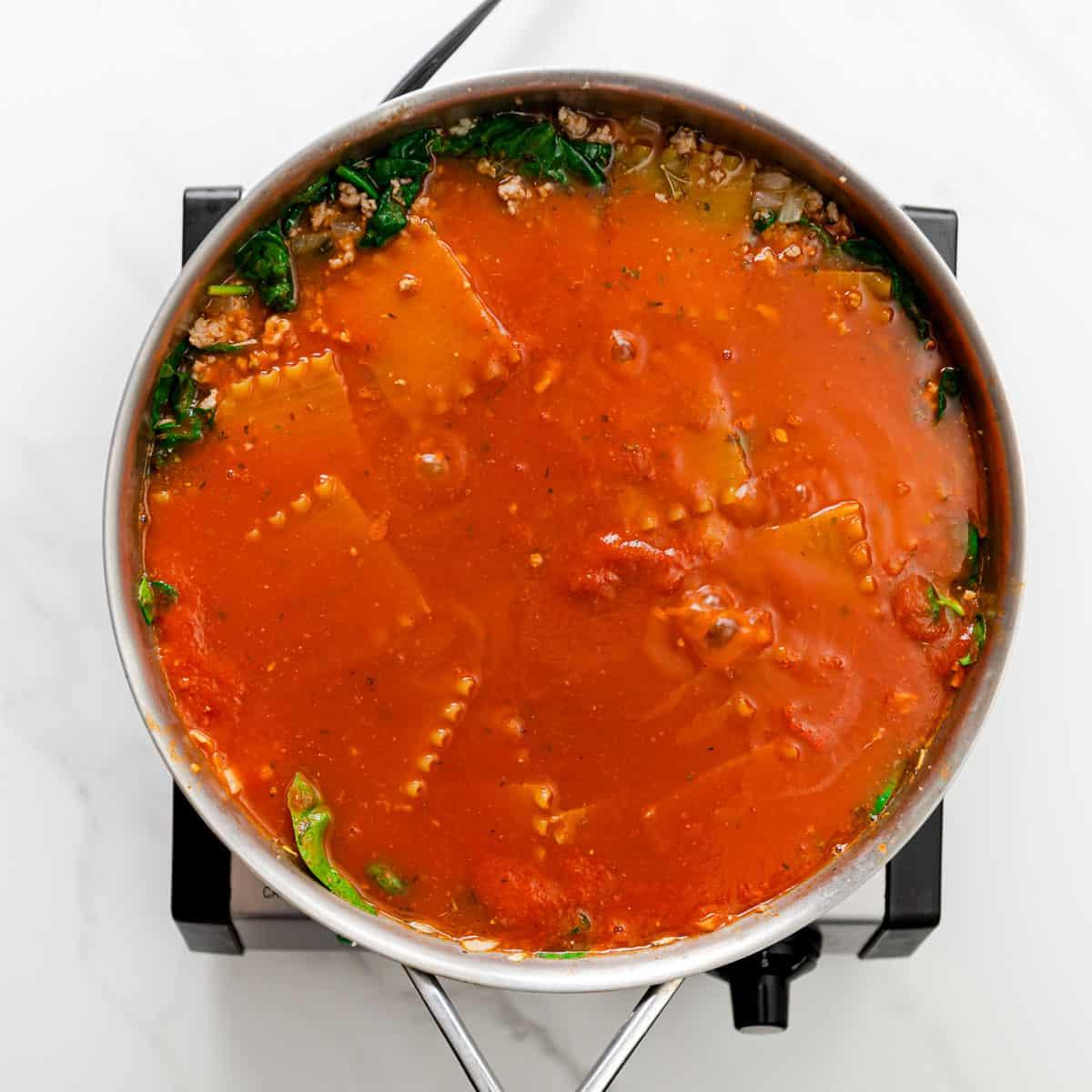 submerging pasta in sauce.