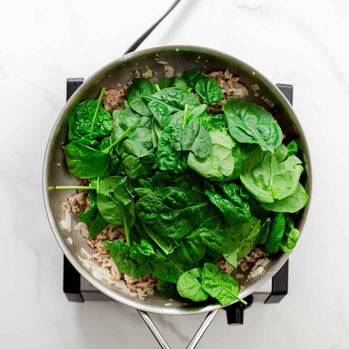 adding spinach to the sauce.