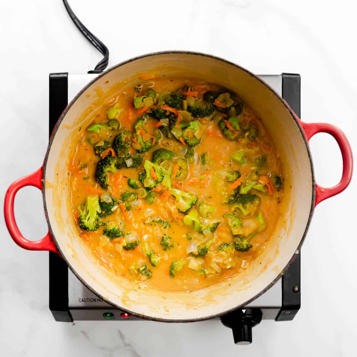 Add low sodium chicken stock into the pot. Bring the mixture to a boil then reduce the heat to medium-low. Simmer, uncovered for 8 minutes or until the broccoli is tender.